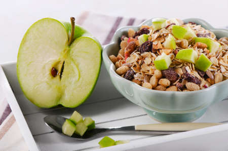 glycemic: Bowl of muesli and  green apple for a nealthy breakfast