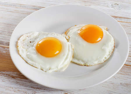 Two fried eggs for healthy breakfast .
