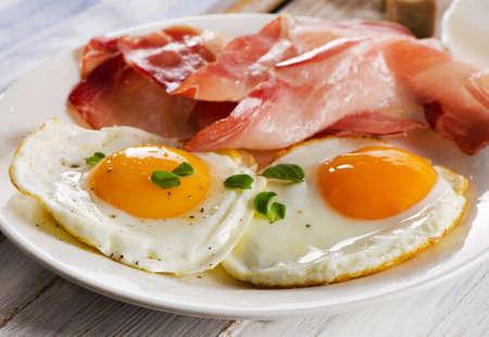 huevos estrellados: Dos huevos fritos y tocino para el desayuno saludable. enfoque selectivo Foto de archivo