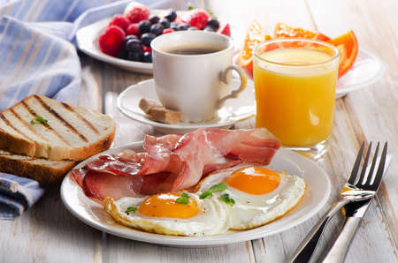 bacon: Coffee cup, Two  eggs  and bacon for healthy breakfast.