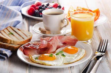 comida inglesa: Taza de café, dos huevos y tocino para el desayuno saludable.