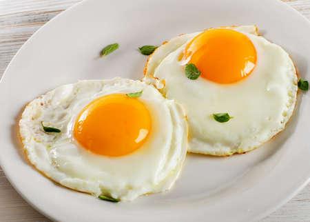 Twee gebakken eieren op witte plaat voor gezond ontbijt.