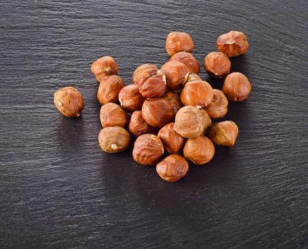 cobnut: Heap of hazelnuts on a dark background. Stock Photo