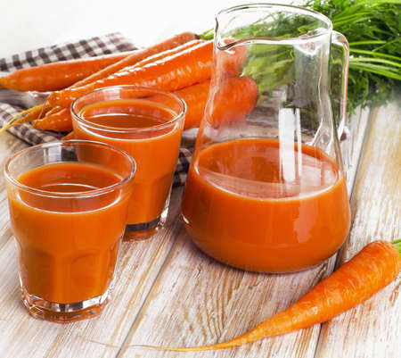 glasses of carrot juice and fresh carrots on a wooden board. photo