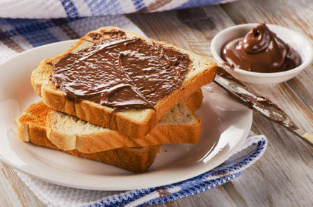 Fresh Toast with chocolate spread on a white plate. photo
