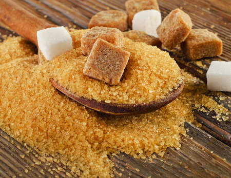 Brown cane sugar on   wooden board. Selective focus Stock Photo