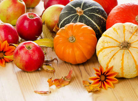 Pumpkins with red apples and  fall leaves. Selective focus