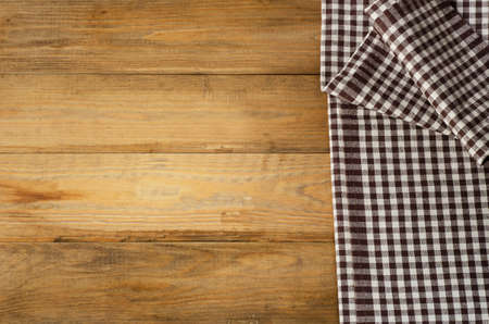 dishcloth: Brown checkered Tablecloth on  wooden background.