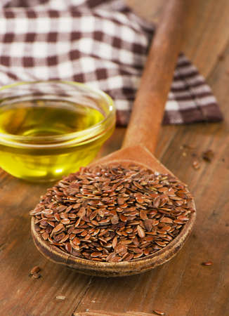 brown flax: Brown flax seeds on spoon and flaxseed oil  on wooden table. Stock Photo
