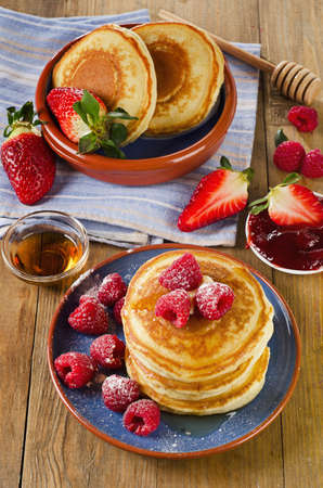 Small pancakes with berries and maple syrup. Top view photo