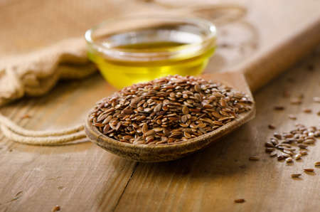brown flax: Brown flax seeds on a spoon and flaxseed oil  on a wooden table.