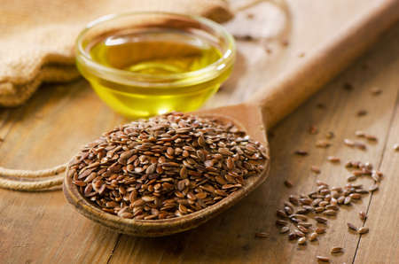 Brown flax seeds on a spoon and flaxseed oil. Stock Photo