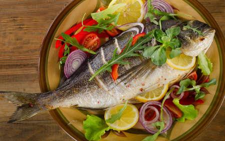 Fried dorado fish on a plate with fresh salad and lemon.  Healthy seafood. photo