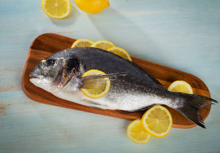 sparus: Raw sea bream with lemon on  a wooden cutting board. Top view Stock Photo
