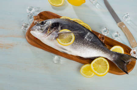 sparus: Raw sea bream with lemon on  a cutting board. Top view