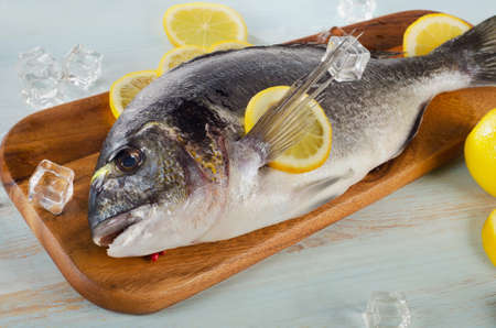 sparus: Raw dorado with lemon on  a cutting board. Stock Photo