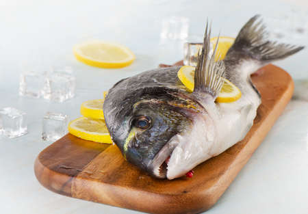 Raw fish with lemon on  a wooden cutting board. photo