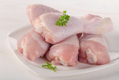 chickens: Fresh chicken legs on a white plate. Stock Photo