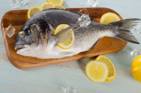 sparus: Raw dorado with lemon on  a wooden cutting board.