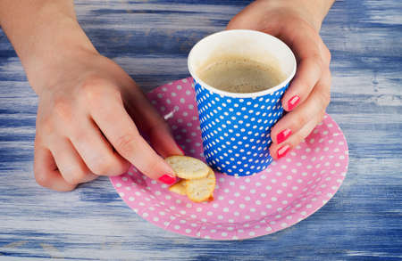 woman hands holding cup of hot coffee and cookie. photo
