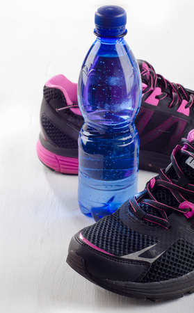 quench: Running shoes and bottle of water - healthy lifestyle.