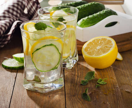 Fresh water with lemon, mint  and cucumber  on  wooden background. Selective focus