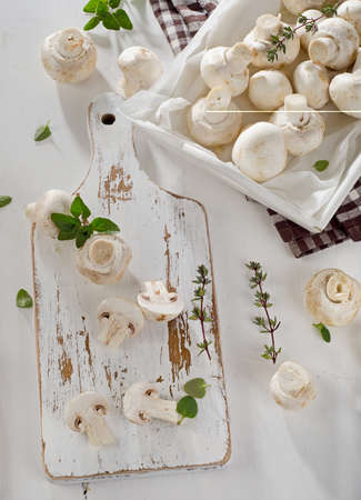 button mushrooms: Whole white button mushrooms  on a wooden board. Overhead view