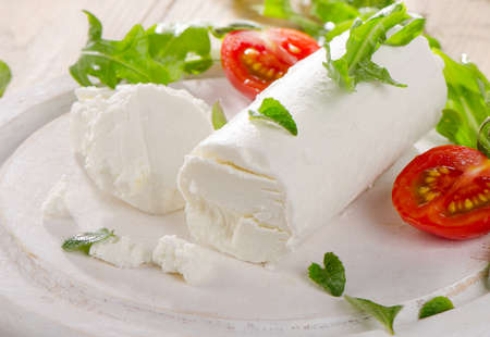 cabras: Queso de cabra con ensalada fresca y tomates en una tabla de madera blanca. Enfoque selectivo