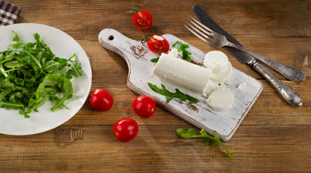 Goat cheese with fresh salad and tomatoes on  a old wooden table. Stock Photo