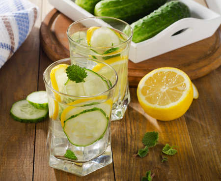 Water with lemon, mint  and cucumber  on  wooden background. Selective focus