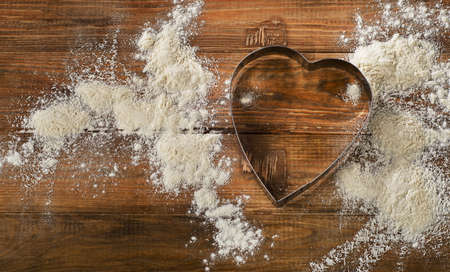 cookie cutter: Flour and Heart-shaped cookie cutter on a worn wooden  desk. Stock Photo