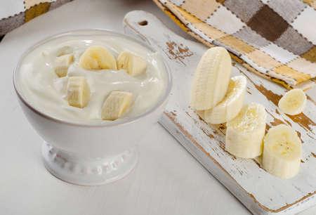 白い木製テーブルの上の白いボウルにバナナとヨーグルト。 写真素材