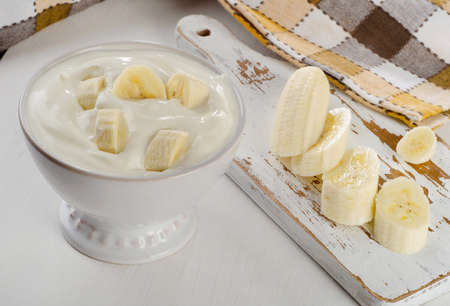 yogurt natural: Yogur con el pl�tano en un plato blanco sobre la mesa de madera blanca.