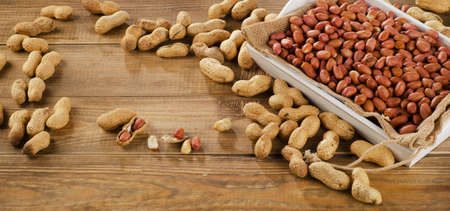 goober: Peanuts in a white box on old  wooden table. Stock Photo