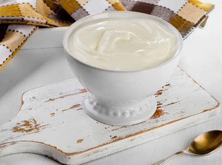 木製テーブルの上の白いボウルでギリシャのヨーグルト。