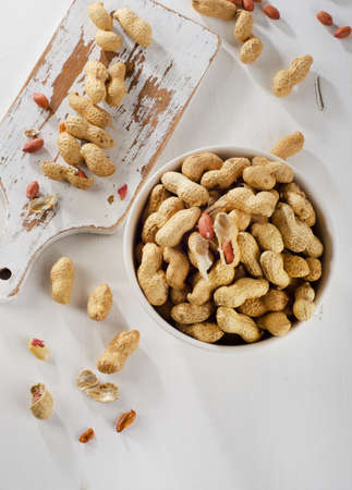 goober: Peanuts in shells on a  white wooden background. Top view