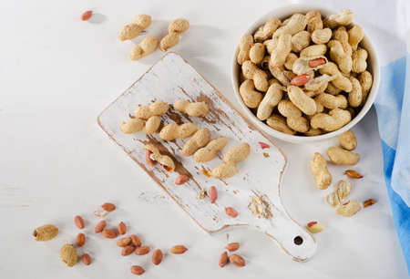 goober: Peanuts in shells on a    white wood background. Top view