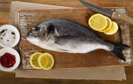 sparus: Fresh sea bream with lemon on  a wooden cutting board.
