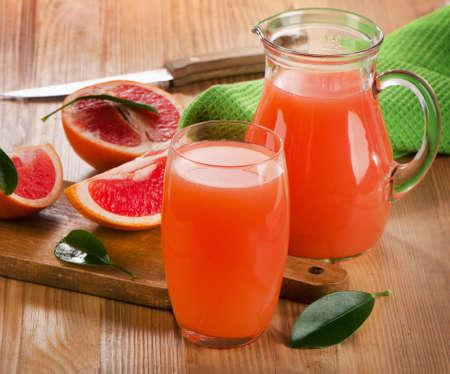 pomelo: El zumo de pomelo en una mesa de madera rústica. enfoque selectivo Foto de archivo