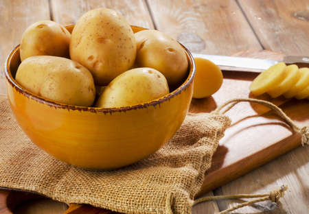 l natural: New potatoes in a bowl on rustic wooden table