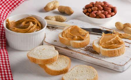 cacahuate: Tostadas con mantequilla de man� y man� en una tabla de madera.