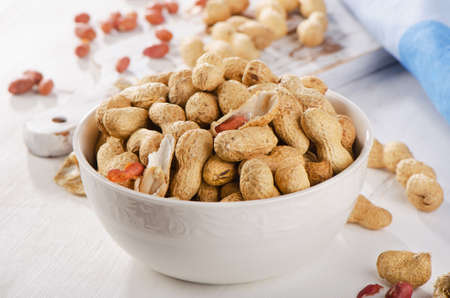 goober: Peanuts in shells in  white bowl. Selective focus Stock Photo