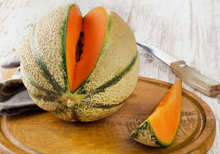 sweet segments: Ripe melon  on  wooden table. Selective focus