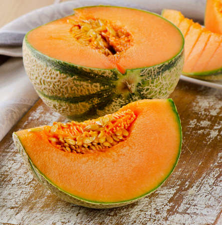 sweet segments: Fresh cantaloupe melon on wooden board