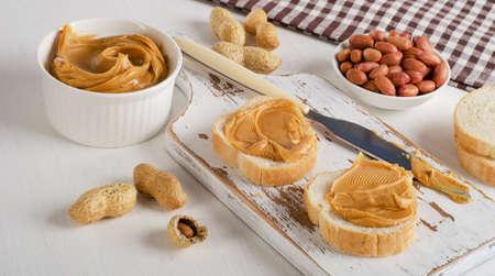 mantequilla: Tostadas con mantequilla de man� y man� en una tabla de madera blanca.
