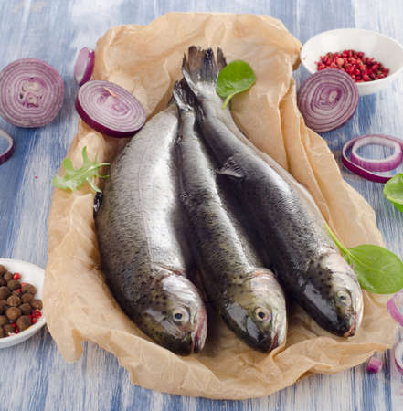 salmon fishery: fresh trouts with spices and seasonings on  a table.