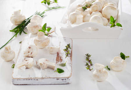 button mushrooms: Fresh whole white button mushrooms on a wooden cutting board Stock Photo