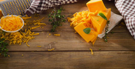 cheddar: Cheddar Cheese on a rustic wooden background