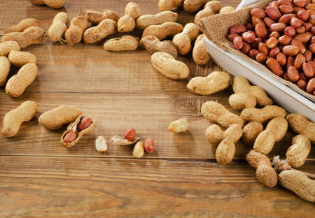 goober: Peanuts in a white box on  wooden table. Stock Photo