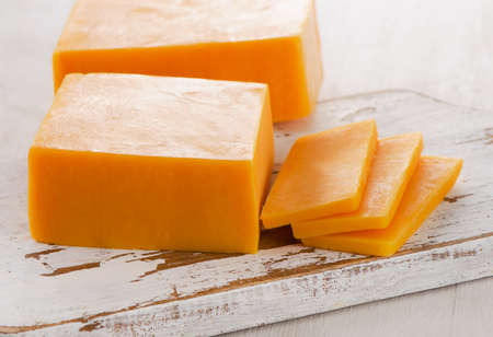 Cheddar Cheese on  white wooden Cutting Board. Selective focus